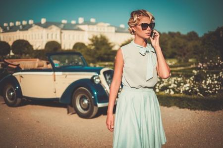 Señora hermosa con el teléfono móvil cerca convertible clásico