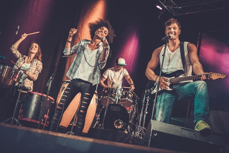 Multiracial music band performing on a stage Reklamní fotografie