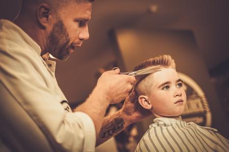 理髪店で小さな男の子の訪問ヘアスタイリスト