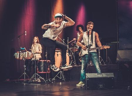 Multiraciale muziekband presteren op een podium Stockfoto