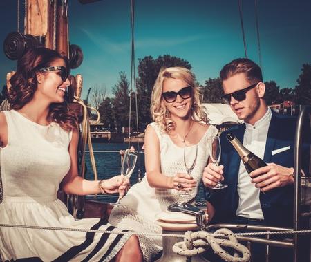 豪華ヨットで楽しんでスタイリッシュな裕福な友人 写真素材