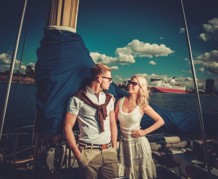Stylish wealthy couple on a yacht 免版税图像