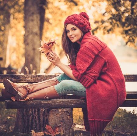 秋の公園でニットのコートを着ている美しい女性