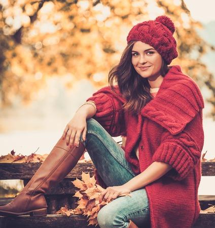Mooie vrouw die gebreide jas in de herfst park