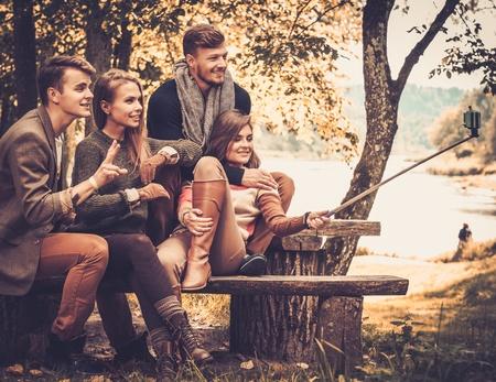 Amigos alegres en otoño toma parque selfie