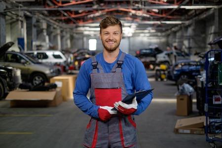 Cheerful serviceman in a car workshop Archivio Fotografico