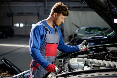 Mechanic with oil filling cork near open hood in a workshop Фото со стока