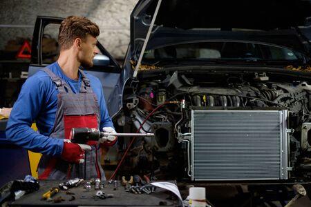 Mechanic with pneumatic tool in a workshop Standard-Bild