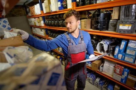 Trabajador en un almacén de piezas de repuesto automotriz Foto de archivo - 46116247