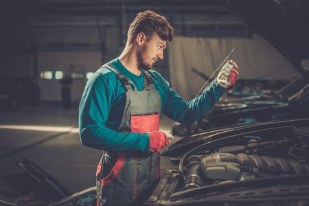 Mechanic checking oil level in a car workshop Stock Photo