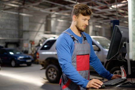 Specialist near car diagnostic pc in a workshop Stock Photo