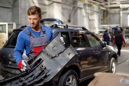 Mecánico con parachoques del coche en un taller