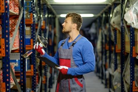 Arbeider op een auto-onderdelen magazijn