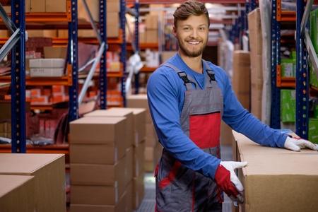 Portier die dozen in een magazijn Stockfoto