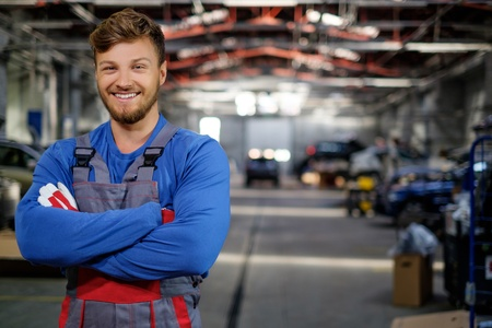 Cheerful serviceman in a car workshop Imagens