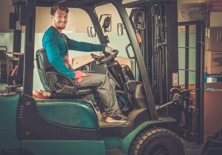 Man driving forklift truck on a warehouse