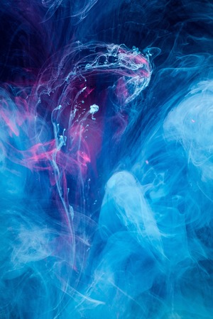 Smoky blue and pink ink in motion on water isolated on black