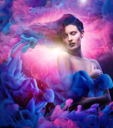 Beautiful woman with magnificent galaxy hair in blue, pink clouds with spiritual light in the middle. Imagens - 49744156
