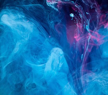 Rokerige blauw en roze inkt in beweging op het water geïsoleerd op zwart