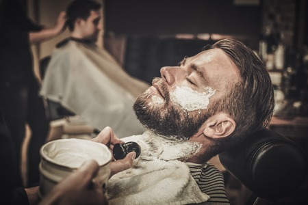 Client during beard shaving in barber shop 스톡 콘텐츠
