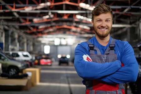 Cheerful serviceman in a car workshop Banco de Imagens