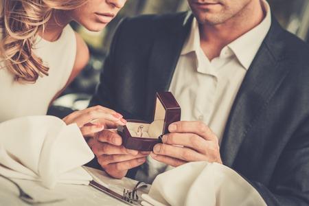 Hombre cuadro de la celebración con la toma de anillo de proponer a su novia Foto de archivo - 50580622