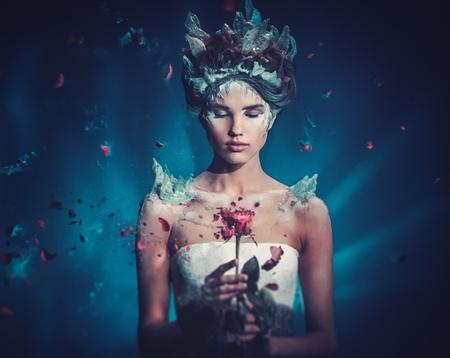 Zima piękna fantazja portret kobiety. Piękna młoda model dziewczyny i podmuch zamrożone róży.