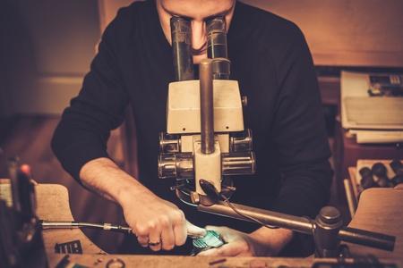 Bijoutier regardant l'anneau à travers un microscope dans un atelier.
