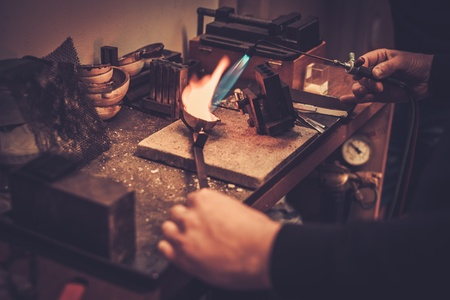 Goldsmith melting gold to liquid state in crucible with gasoline burner. Stockfoto
