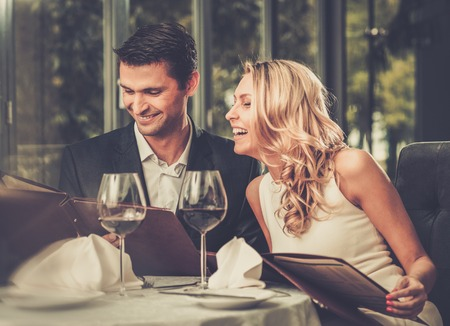 Cheerful couple with menu in a restaurant Foto de archivo