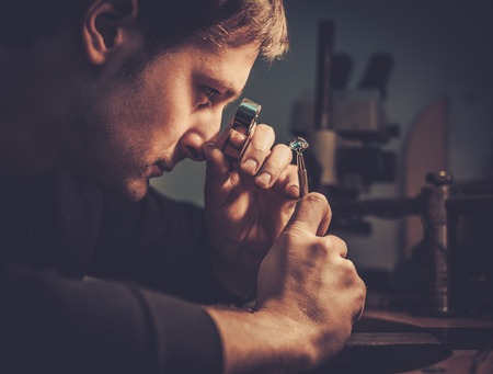Joyero mirando el anillo a través de microscopio en un taller. Foto de archivo - 50662043