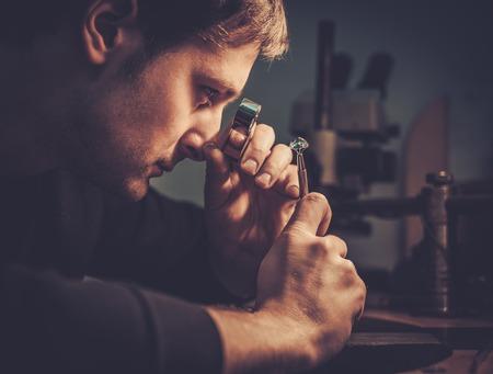 Jubiler patrząc na ringu przez mikroskop w warsztacie.