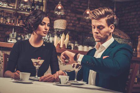 Pareja rica con estilo que se postre y café juntos en un restaurante.