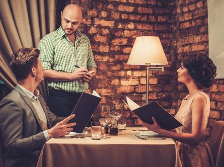 레스토랑에서 세련 된 부유 한 커플에서 주문을 받고 웨이터.