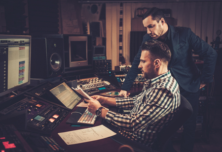 Sound engineer and producer working together at mixing panel in the boutique recording studio. Standard-Bild