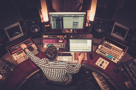 inżynier dźwięku pracujący w panelu mieszania w studiu nagraniowym butik. Zdjęcie Seryjne