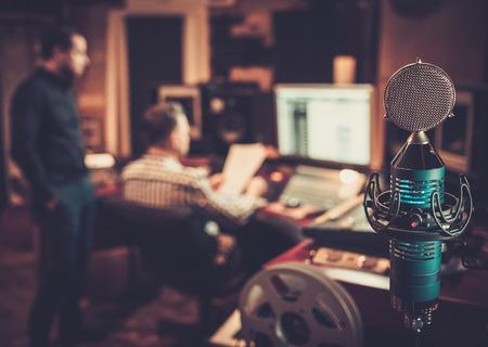 Geluidstechnicus en producer samen te werken op mengpaneel in de boetiek opnamestudio.