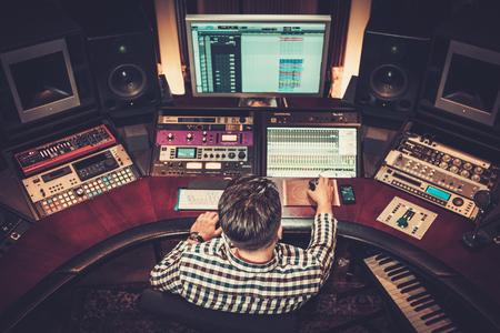 Ingegnere del suono che lavora a mescolare pannello in studio di registrazione boutique.