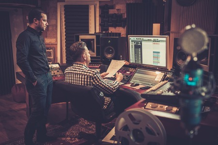 Sound engineer and producer working together at mixing panel in the boutique recording studio. Foto de archivo