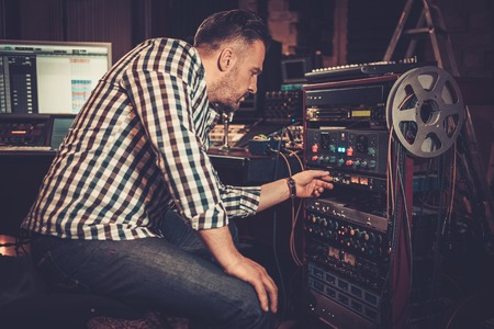 Sound engineer working with professional audio equipment in the boutique recording studio. Zdjęcie Seryjne