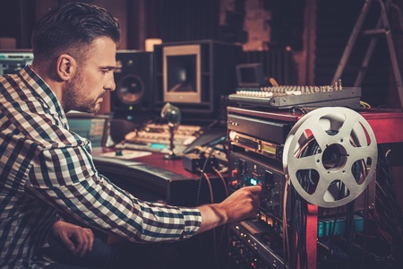 Sound engineer working with professional audio equipment in the boutique recording studio. Stock Photo