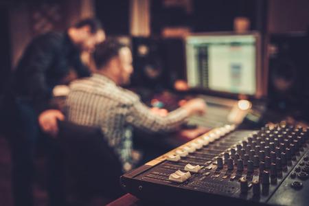 サウンドエンジニアとプロデューサーは、ブティックレコーディングスタジオのミキシングパネルで一緒に働いています。