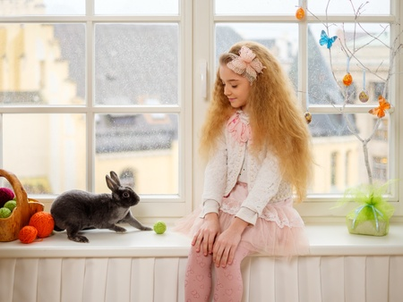 Beautiful little girl sitting on a windowsill and playing with Easter bunny. Stok Fotoğraf - 51873365