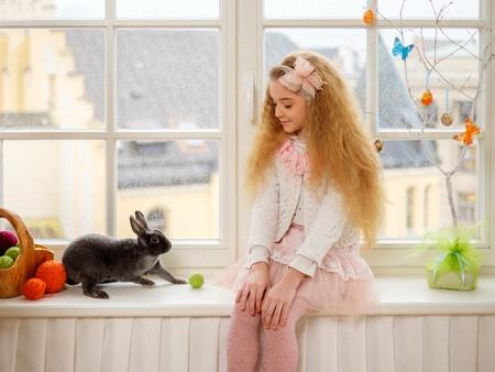 Niña hermosa que se sienta en el alféizar de una ventana y jugando con el conejito de Pascua. Foto de archivo - 51873365