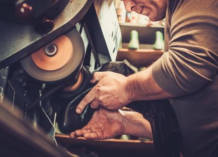 Shoemaker repairs shoes in the studio craft grinder machine.