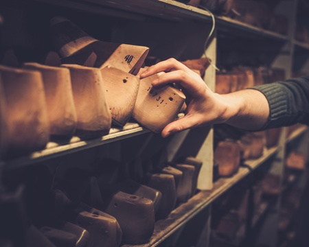Various of vintage wooden shoe lasts in a row on the old shelves.