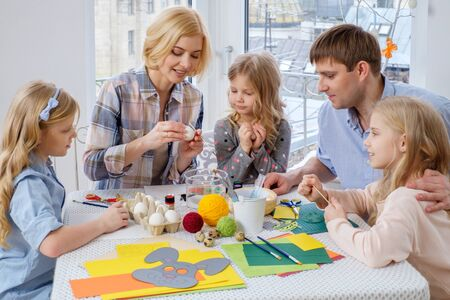 Cheerful family having fun painting and decorating easter eggs.