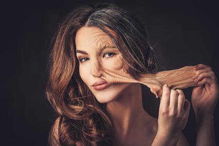 Invecchiamento e il concetto di cura della pelle. Metà vecchia metà giovane donna, si toglie la vecchia pelle del viso.