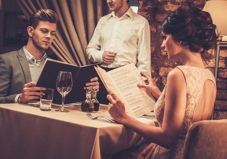 Waiter explaining the menu to stylish wealthy couple in restaurant. Standard-Bild