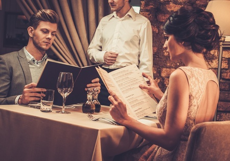 Waiter explaining the menu to stylish wealthy couple in restaurant. Zdjęcie Seryjne